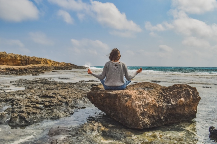 woman meditating on a rock at the ocean